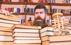 Teacher or student with beard sits at table with books, defocused. Bibliophile concept. Man on confused face between. Piles of books, while studying in library stock photography