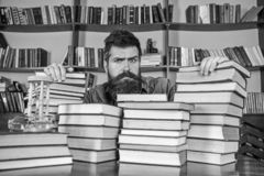 Teacher or student with beard sits at table with books, defocused. Man on serious face between piles of books, while. Studying in library, bookshelves on stock photography