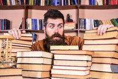 Teacher or student with beard sits at table with books, defocused. Man on shocked face between piles of books, while. Studying in library, bookshelves on stock photos