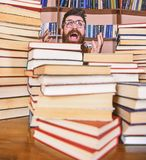 Teacher or student with beard wears eyeglasses, sits at table with books, defocused. Scientific discovery concept. Man. On excited face between piles of books royalty free stock image