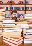 Teacher or student with beard wears eyeglasses, sits at table with books, defocused. Scientific research concept. Man on. Surprised face between piles of books stock image