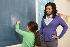 Teacher and Student at Blackboard Stock Images
