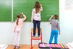 Teacher and student at the blackboard, math class Stock Photos