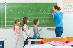 Teacher and student at the blackboard, math class Stock Image