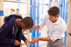 Teacher With Student In Carpentry Class Fitting Door Lock Stock Image
