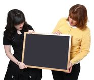Teacher and Student with Chalkboard. Teacher and high school student holding chalkboard over white.  Looking at chalkboard Royalty Free Stock Photography