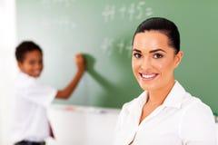 Teacher student chalkboard. Pretty elementary school teacher and student in front of chalkboard Stock Image