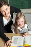 Teacher and student in the classroom with a book. Before him. Both laugh at the camera Royalty Free Stock Photography