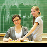 Teacher and student in the classroom - square. Young friendly teacher and pupil in the classroom. The teacher sits at the desk in front of the blackboard. Next Royalty Free Stock Images