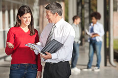 Teacher And Student Discussing Over Book On Campus. Mature male teacher and student discussing over book on college campus Royalty Free Stock Images