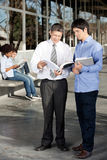 Teacher And Student Discussing Over Book On. Full length of male teacher and student discussing over book on university campus Stock Photography