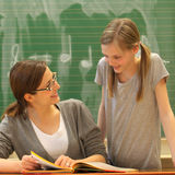 Teacher and student in education at schoo. L. The smiling teacher says the student something from a book - both smiling - square Stock Images