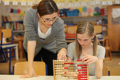 Teacher and student in the elementary school. Teacher and students in the elementary school. The teacher told the school child a task Stock Image