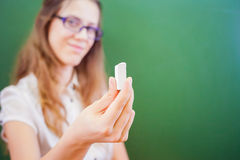 Teacher or student, holding a chalk near green chalkboard Royalty Free Stock Photography