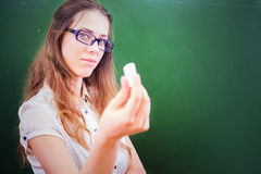 Teacher or student, holding a chalk near green chalkboard Stock Image