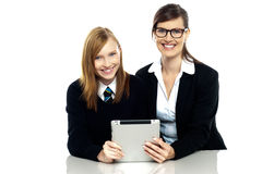 Teacher and student holding tablet device together. Isolated over white Royalty Free Stock Photography