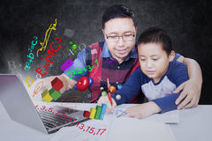 Teacher with student and laptop. Male teacher teaching his student using laptop with formula of science, math, and physics in the class Royalty Free Stock Images