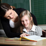 Teacher and student  learn together. Teacher and pupil in classroom learning together Royalty Free Stock Photography