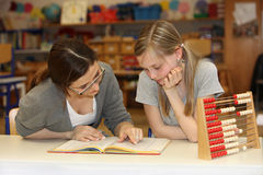 Teacher and student  learning together. Teacher and student sitting at school desk with a textbook on learning together Stock Photos