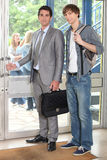 Teacher and student leaving building Royalty Free Stock Image