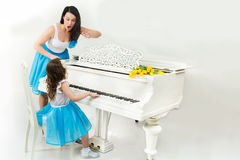 Teacher and student in a music school learning to play the piano. Strict music teacher scolds the student who sits at a white piano in a music school Royalty Free Stock Photography