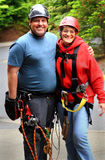 Teacher and Student. An older lady wearing zip line gear standing beside the zipline instructor. Shallow depth of field Royalty Free Stock Images