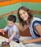 Teacher With Student Painting In Classroom. Portrait of beautiful young teacher with student painting in classroom Stock Photo