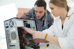 Teacher with student repairing computer. Teacher with student in technology repairing computer Royalty Free Stock Photography