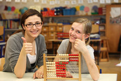 Teacher and a student show at school thumbs up. Teacher and student sitting at a desk at school or in the classroom and both show up the thumb Royalty Free Stock Images