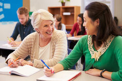 Teacher and student sit together at an adult education class Royalty Free Stock Photography
