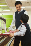Teacher and student talking in school cafeteria Royalty Free Stock Photos