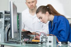 Teacher with student in technology repairing computer. Girl royalty free stock images