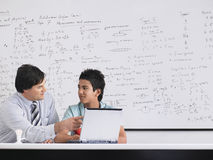 Teacher And Student Using Laptop In Class. Teacher and student using laptop sitting in physics classroom Stock Photos