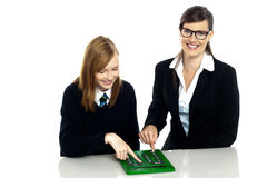 Teacher and student working on calculator. Pretty teacher and student working on a large green calculator together Royalty Free Stock Images