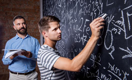 Teacher and student writing on big blackboard with mathematical. Close up of hipster teacher with his student writing on big blackboard with mathematical symbols Royalty Free Stock Photo