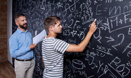 Teacher and student writing on big blackboard with mathematical Stock Photo