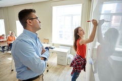 Teacher and student writing on board at school Royalty Free Stock Images