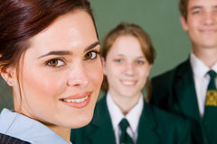 Teacher and students. Beautiful young female high school teacher with her students royalty free stock image