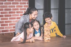 Teacher and students building toy block tower togetherness c. Teacher and students are building toy block tower togetherness classroom royalty free stock image