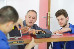 Teacher with students in carpentry class fitting door lock. Apprentice Stock Image