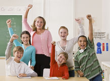 Teacher and students cheering. Teacher and her students raise their hands in the air Royalty Free Stock Image