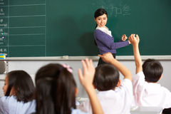 Teacher With Students In Chinese School Classroom Stock Photo