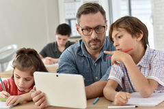 Teacher with students in class using tablet Royalty Free Stock Photo