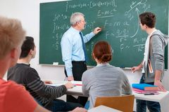 Teacher with students in classroom. Teacher with a group of high school students in classroom stock photography