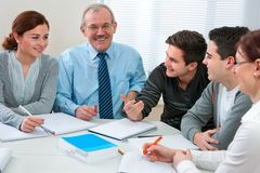 Teacher with students in classroom. Teacher with a group of high school students in classroom Stock Photo