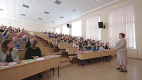 Teacher With Students At The College Lecture Hall