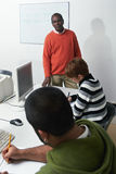 Teacher and students in computer class. Computer class with male indian teacher looking at camera and students doing exam. Vertical shape, focus on background Royalty Free Stock Photography