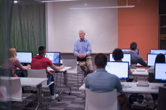 Teacher and students in computer lab classroom Stock Image