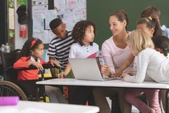 Teacher and students discussing over laptop in classroom royalty free stock photo
