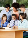 Teacher And Students Discussing Over Mobilephone Stock Photos